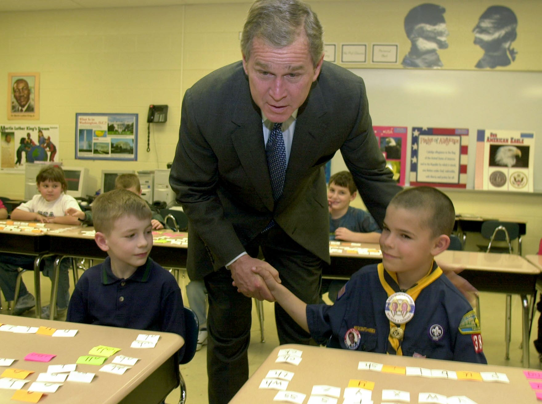 """President George Bush shakes hands with Christopher Overstreet as he tells photographer, """"you know I was a scout."""" President Bush visited Pam Reed's second grade class at Townsend Elementary School Wednesday morning.  To the left of Bush is Bradley Allen."""
