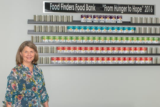 """Katy Bunder, of Food Finders, posses in front of the """"From Hunger to Hope"""" donor wall."""