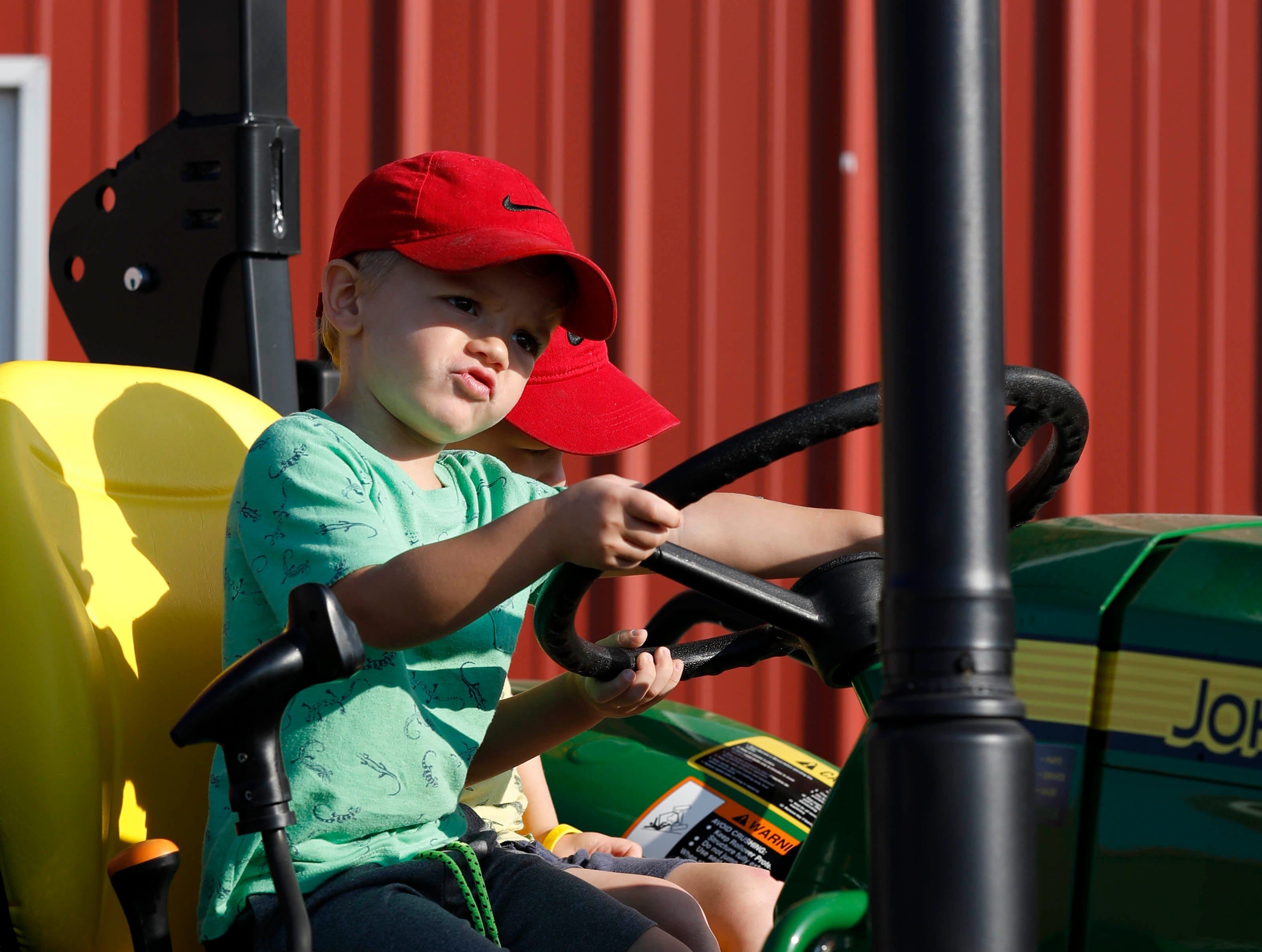 Austin Greene, 4,  sits at the wheel of a tractor with his brother Eli Greene, 3, Monday, Oct. 8, 2018, at the Fairfield County Fair in Lancaster.