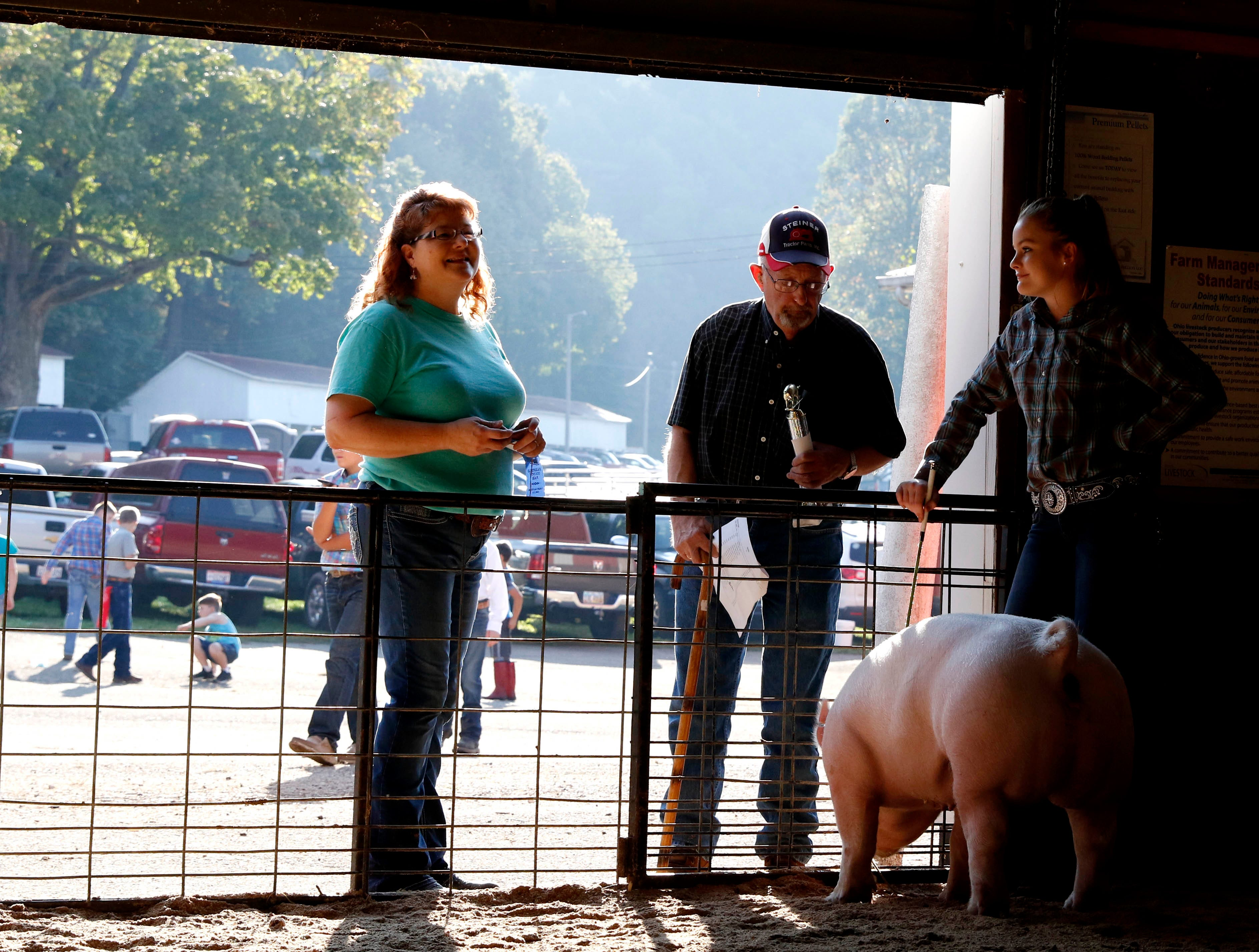 Steve Smith, center, congratulates Kaylee Sharp, 15, from Stoutsville, as he talks to her and her mother Joy Sharp, left, Monday morning, Oct. 8, 2018, after Kaylee took second place in class 4 with her hog Iris at the Fairfield County Fair in Lancaster.
