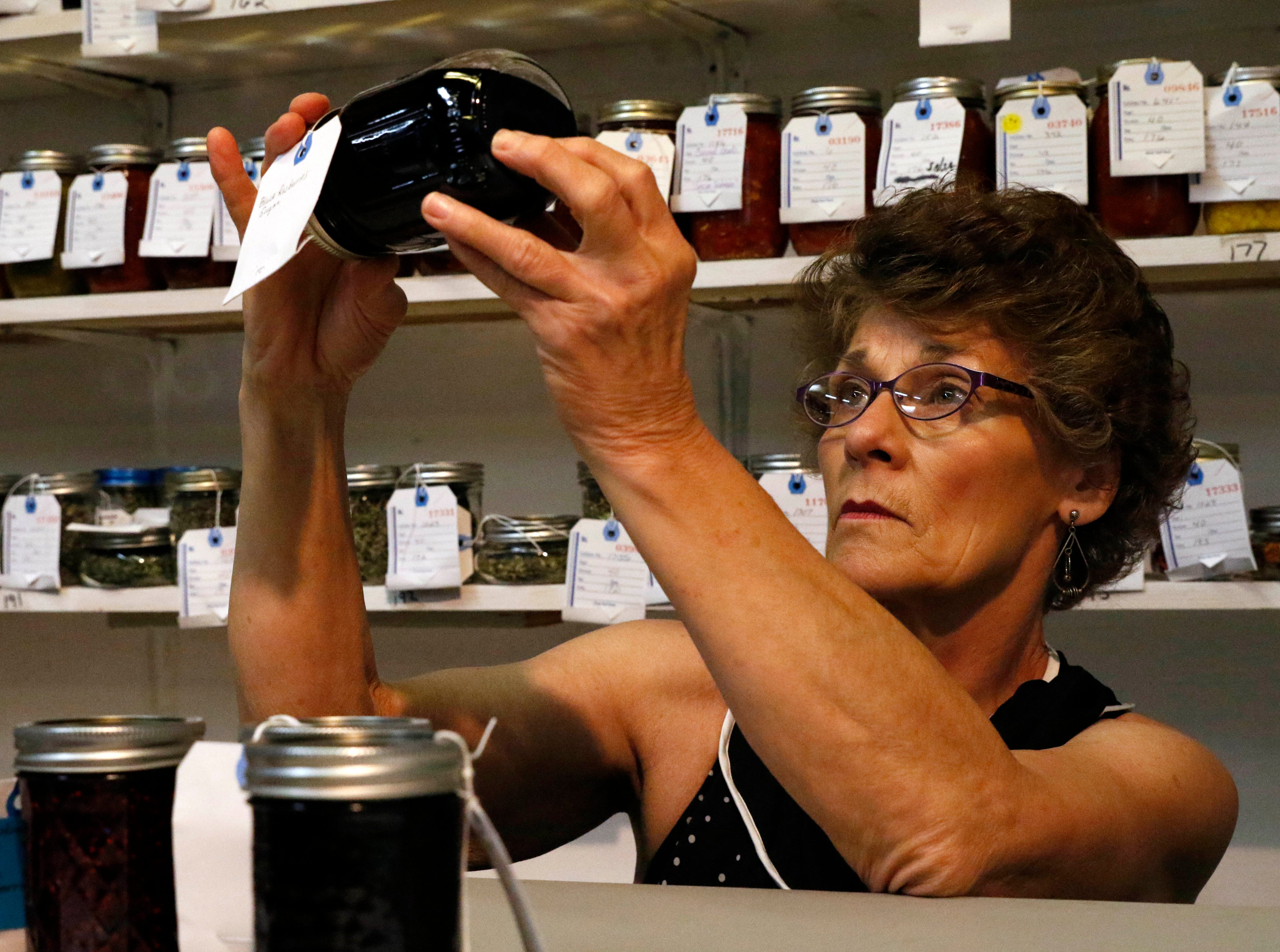 Candy Shuster, from Somerset, judges jars of jam Monday morning, Oct. 8, 2018, in the Art Hall at the Fairfield County Fair in Lancaster. Shuster, a retired Ohio State University extension educator in Perry County, was judging canned goods.