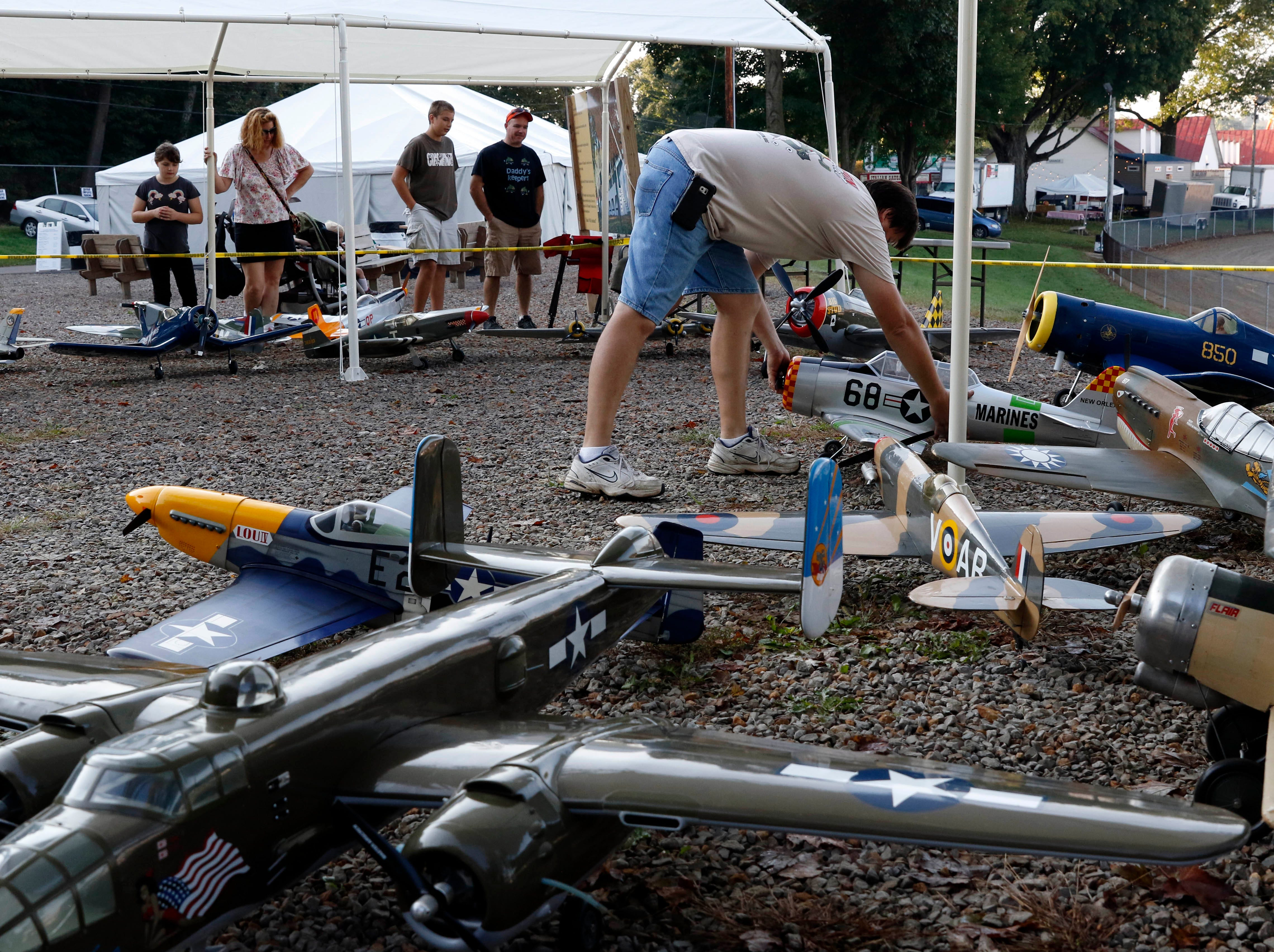 Jamie Thimmes, sets up radio controlled airplanes Monday morning at the Fairfield County Fair in Lancaster. Thimmes and other members of the Flying FORKS (Fairfield Ohio Radio Kontrol Society) were setting up dozens miltary model planes for Veterans Day.