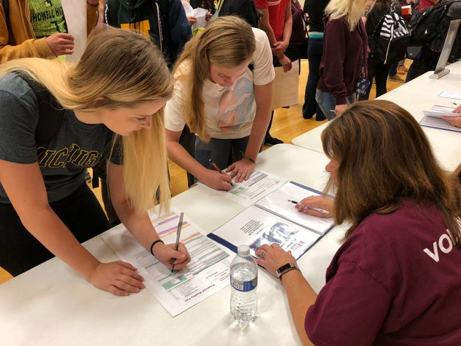 Students review different car options during the Livingston Oakland County Financial Reality Fair on Monday Oct. 8, 2018 at Howell High School.