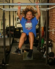 Nick Porter of South Lyon swings from a bar at Iron Grip Ninja in Howell. He is one of four children who train at the gym who competed on American Ninja Warrior Junior, which begins airing Saturday.
