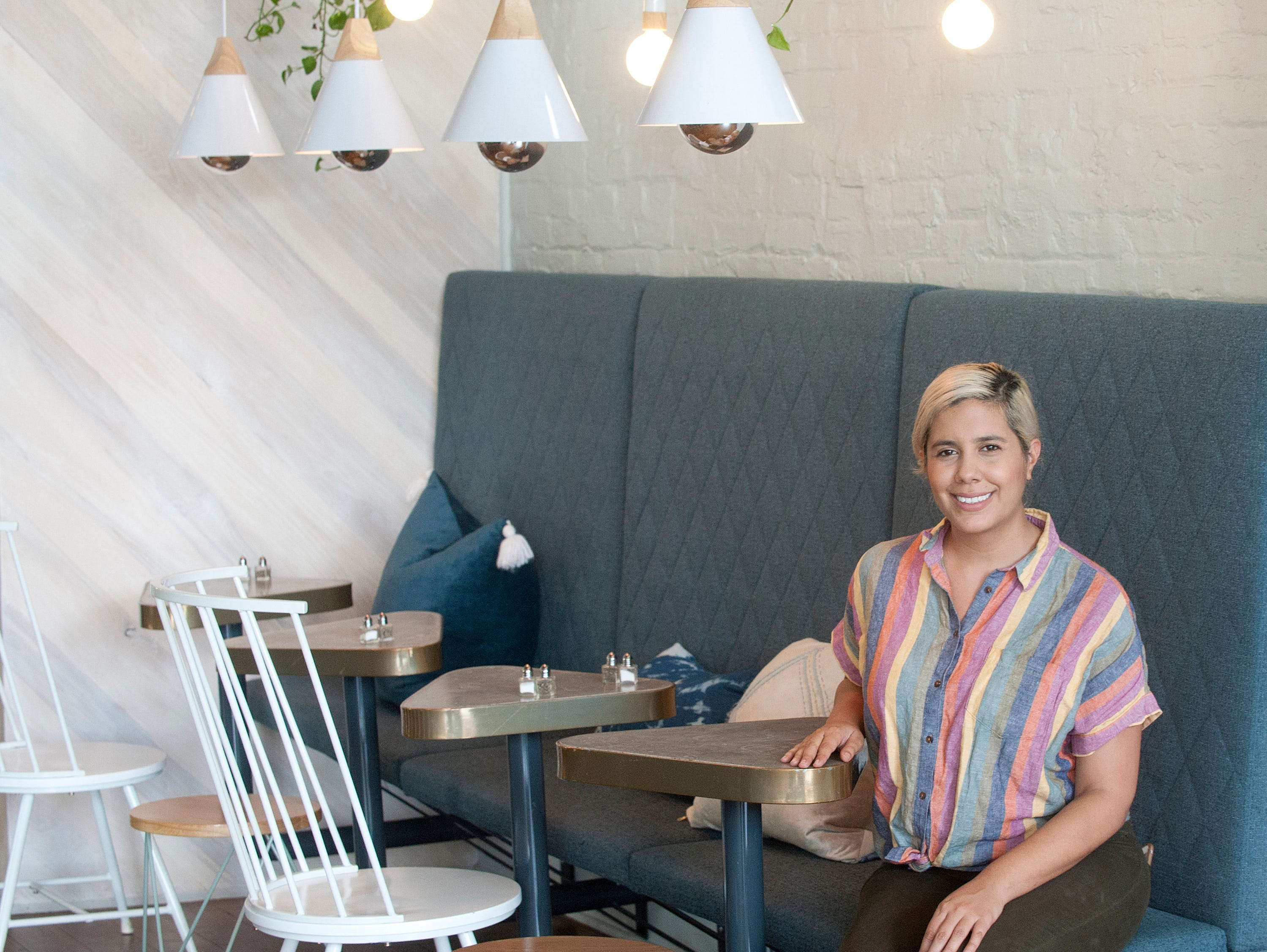 Catherine Mac Dowall who co-owns Naive, a restaurant on E. Washington St. with her husband Michael Kerrigan sits in the eatery's dining room.September 20, 2018