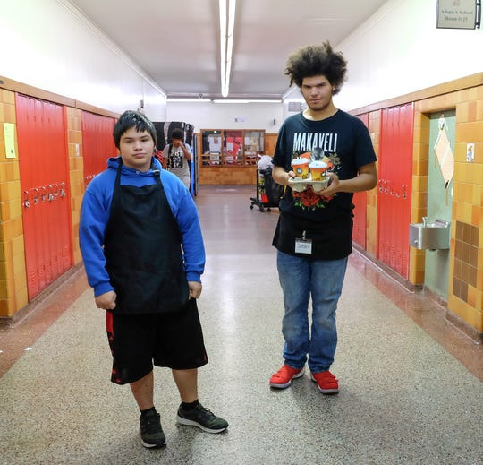 Zackari Hustin, left, and Sergio Gomez team up to deliver coffee to teachers during 1st period at Sexton High School Monday, Oct. 8, 2018. As part of a special education transitional program students learn what it takes to run a coffee shop.