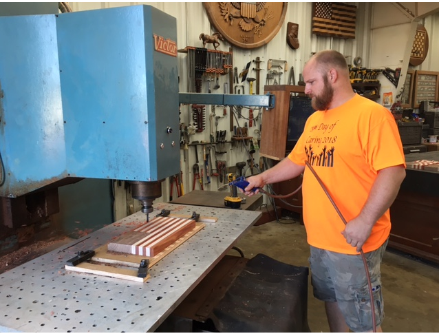 Andrew Rush, of Rush Woodworks of Lexington, Ohio, uses a CNC machine at R.L. Rush Tool & Pattern Inc. in Bucyrus which his father Roger Rush owns, to create the waves in the wooden U.S. flag 3-D sign Monday.