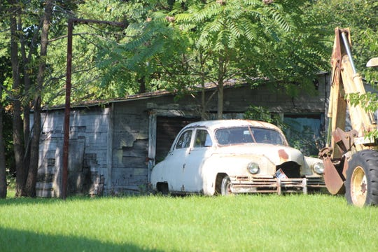 A car sits in a yard behind a Marion house. City officials have proposed changes to the city code that would stiffen penalties for junk cars.