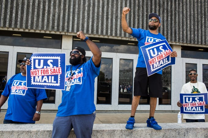 October 08 2018 - Clarence Ballentine Jr., second from left, and Jason Coates, second from right, both truck drivers for the U.S. Postal Service, get a passing truck to honk its horn while they rallied on Monday along with coworkers and supporters in front of the Memphis Post Office. Participants sounded an alarm against a proposal announced in June by the White House's Office of Management and Budget to privatize the U.S. Postal Service.