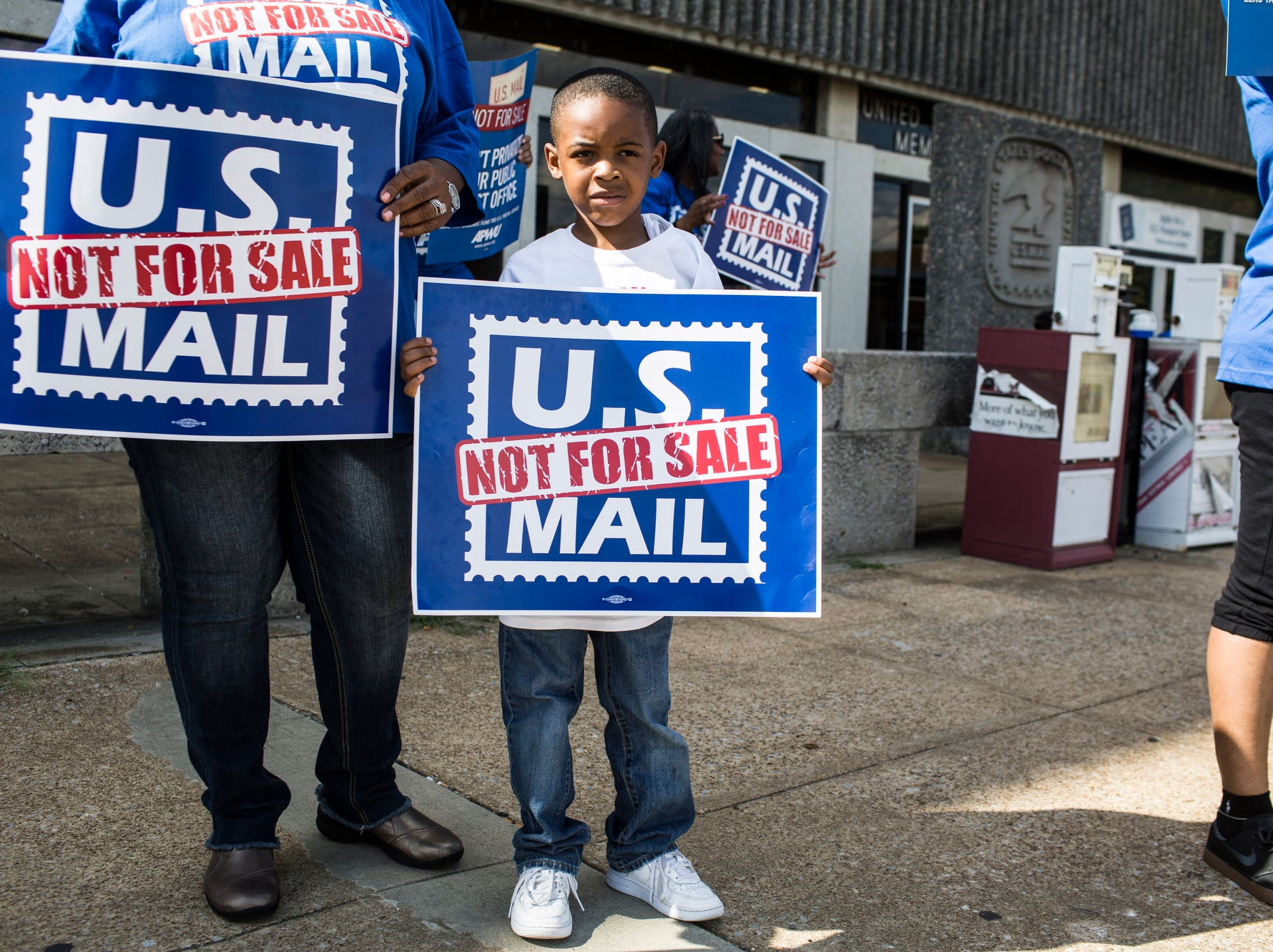 October 08 2018 - Octavious Woods, 6, stands with his grandmother, Bonita Tate, left, while U.S. Postal Service employees, joined by community supporters, rallied on Monday in front of the Memphis Post Office. Participants sounded an alarm against a proposal announced in June by the White House's Office of Management and Budget to privatize the U.S. Postal Service.