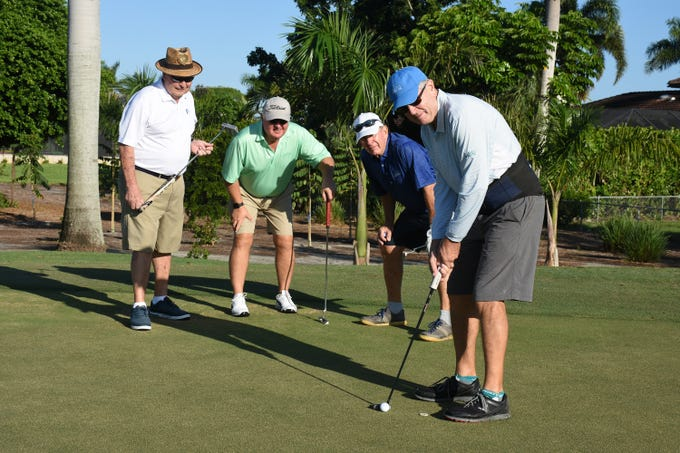 WAyne Purvis, left, Michael Hook, and Tom Eiseman help Doug Peterson line up his putt. The Marco Police Foundation held their annual golf event Saturday morning on the Island Country Club course.