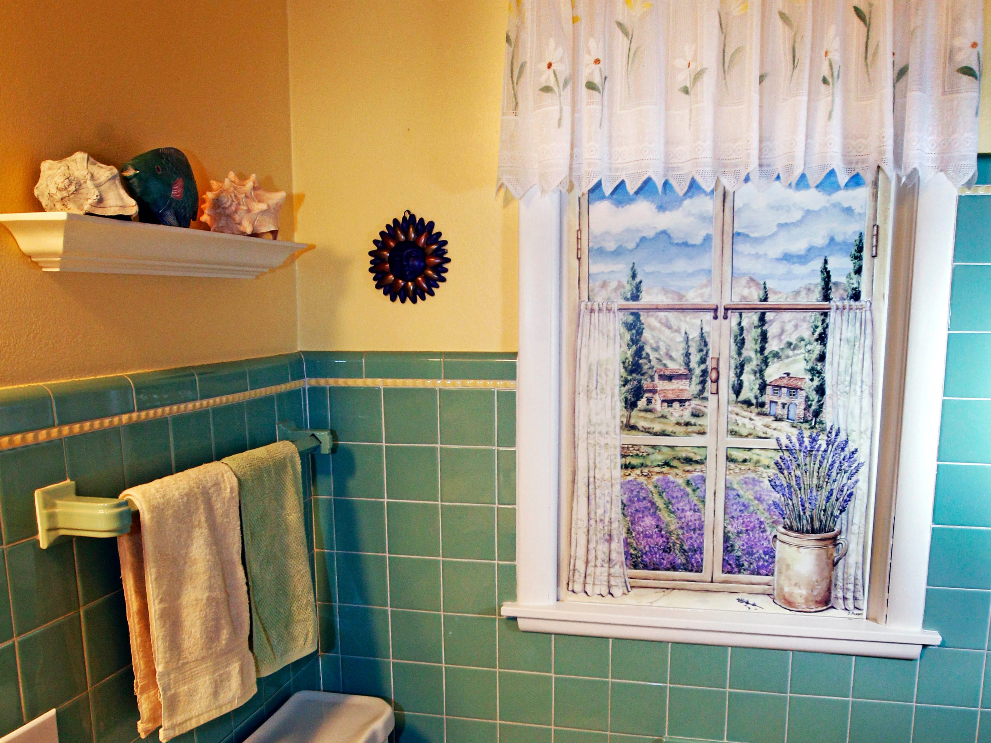 The homeowner deliberately left his bathroom in its original 1955 state. When the home was renovated in 1976, the window was closed off, so she added this painting of a window for effect.
