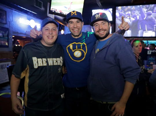 Tim Lynch of Manitowoc, Tyler Sopko of West Bend, and his brother, Travis Sopko of Brookfield, pose for a photo after the final out at Kelly's Bleachers on West Bluemound Road in Milwaukee as the Milwaukee Brewers beat the Colorado Rockies, 6-0, Sunday in Denver to advance to the National League Championship Series.