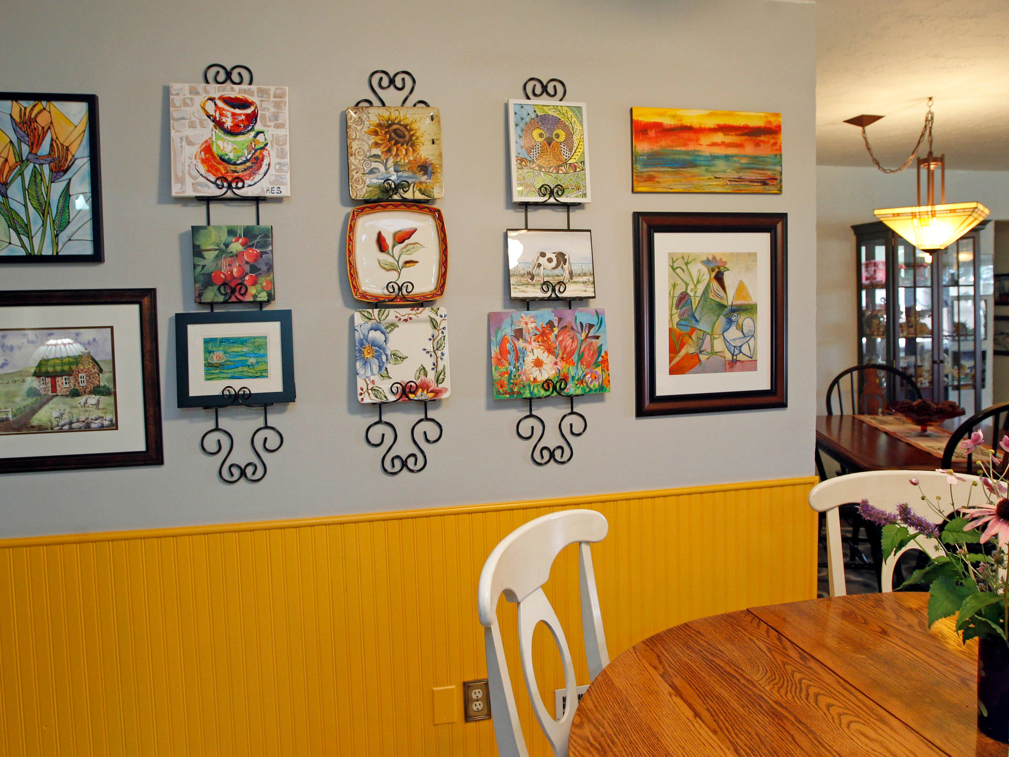 Artwork created by homeowner Ann Sheahan and those of other artists is displayed near the eating area of the kitchen.