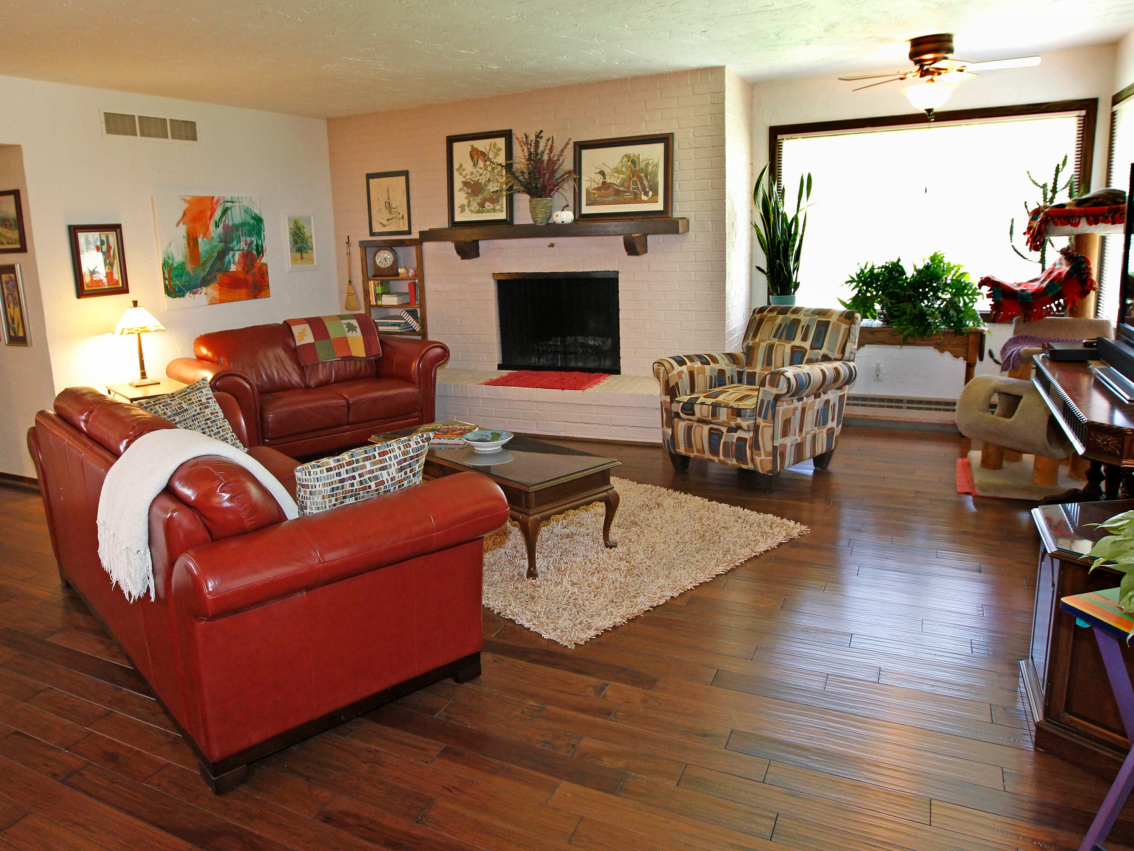 The living room features a fireplace and the homeowner's artwork along with her collection of other art pieces.