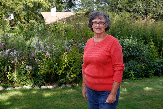 Ann Sheahan, shown in the prairie garden area of her 3/4-acre property, has thrown herself into artwork and gardening in her retirement.