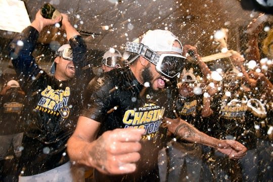Jeremy Jeffress is doused by teammates as they celebrate in the clubhouse after clinching the NLDS vs. Colorado.