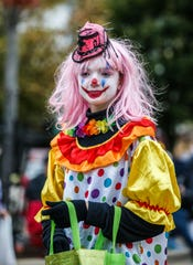 A colorful character from Oconomowoc's Dark Carnival Haunted House hands out candy during the annual homecoming parade on Friday, Oct. 5, 2018. The Dark Carnival announced 2019 will be the haunted house's final season.