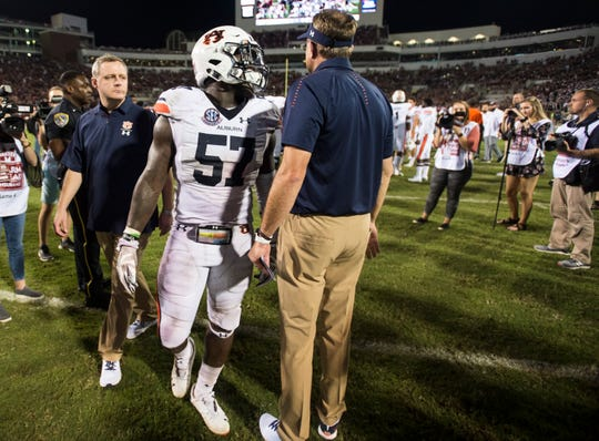 Auburn's Deshaun Davis (57) chats with his head coach Gus Malzahn as he limps off the field  at Davis Wade Stadium in Starkville, Miss., on Saturday, Oct. 6, 2018. Mississippi State defeated Auburn 23-9.