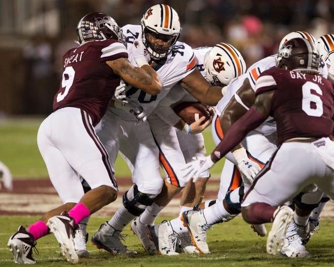 Auburn's Calvin Ashley (70) attempts to block for his quarterback Jarrett Stidham (8) against Mississippi Sate at Davis Wade Stadium in Starkville, Miss., on Saturday, Oct. 6, 2018. Mississippi State defeated Auburn 23-9.