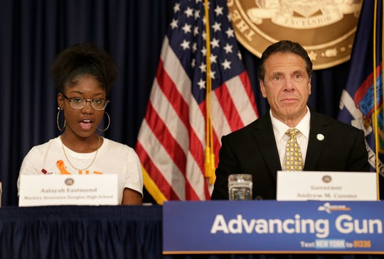 New York Gov. Andrew Cuomo listens as Aalayah Eastmond, a student at Marjory Stoneman Douglas High School and survivor of the mass shooting there, speaks during a news conference in New York on June 5.