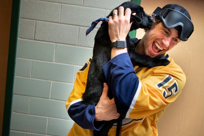 Predators forward Craig Smith is greeted by Stanley, a 10-week-old puppy with Leader Dogs for the Blind, before a game of goalball at the Tennessee School for the Blind on Monday. Goalball is a sport designed specifically for athletes with vision impairment.