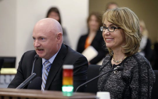Former Arizona Congresswoman Gabrielle Giffords, right, smiles briefly as her husband, retired NASA space shuttle commander Mark Kelly, testifies before a Washington state House panel on Jan. 28, 2014, in Olympia, Wash.