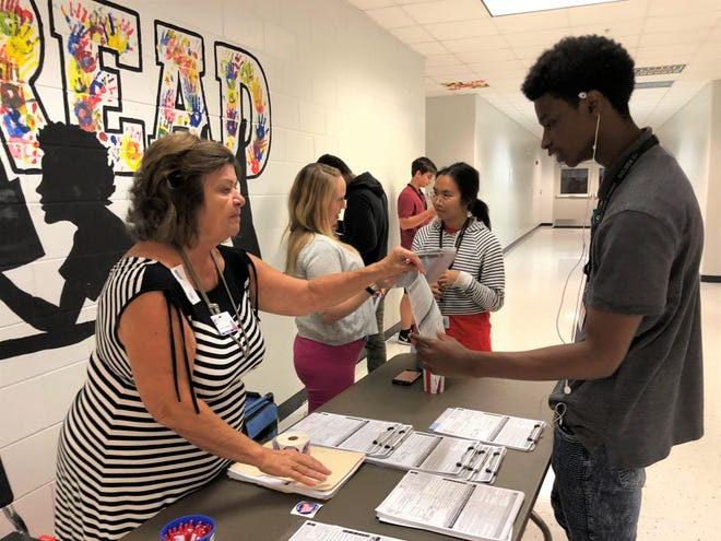 Pam Friedrick helps a student register to vote at Golden Gate High School in October 2018 in Collier County, Florida. Proposition 18 on the Nov. 3, 2020, California ballot would allow some 17-year-olds to register to vote and even run for office.