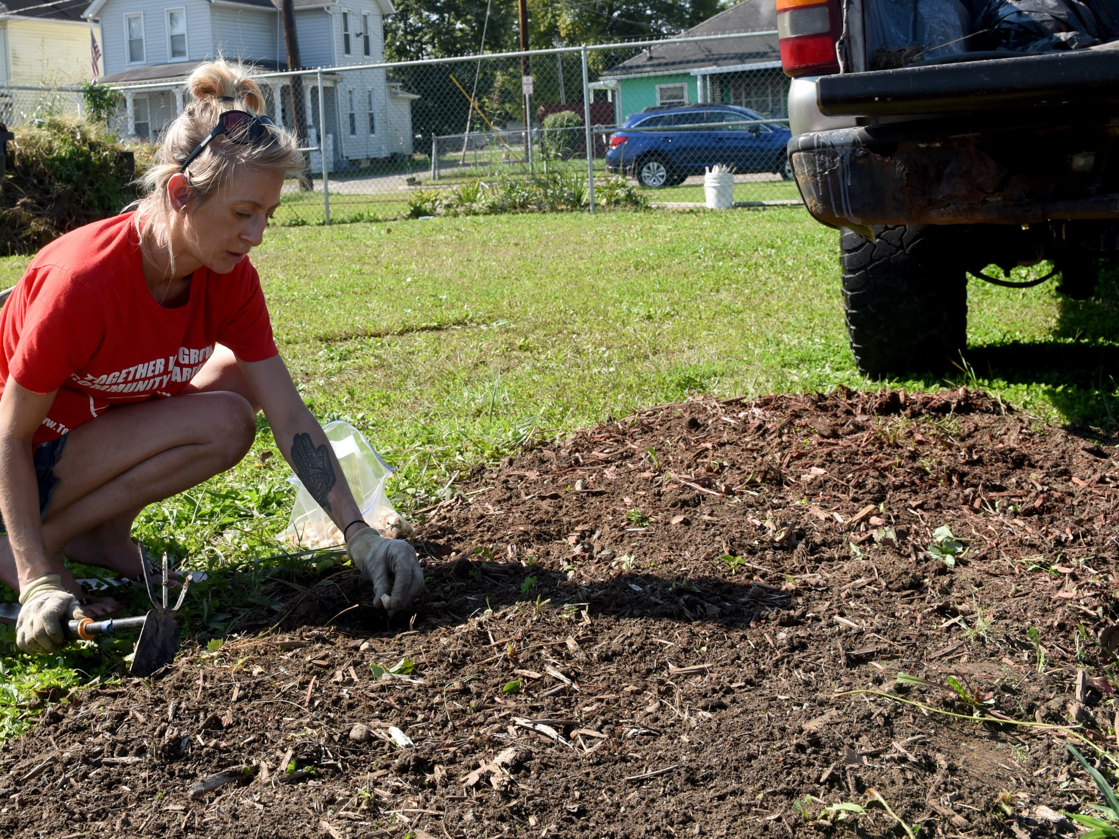 Sarah Thomas, of Together We Grow Gardens, demonstrates to Park National Bank employees how to plant garlic at the garden on East Main Street in Newark. Bank employees volunteered at the garden to prepare it for winter as part of the company's PNB Cares initiative on Monday, Oct. 8, 2018. Employees worked on over 70 projects for organizations in Central Ohio communities. Local projects also included landscaping at the Weathervane Playhouse, organizing books for the Licking County Library, and painting for the Licking County Coalition for Housing.