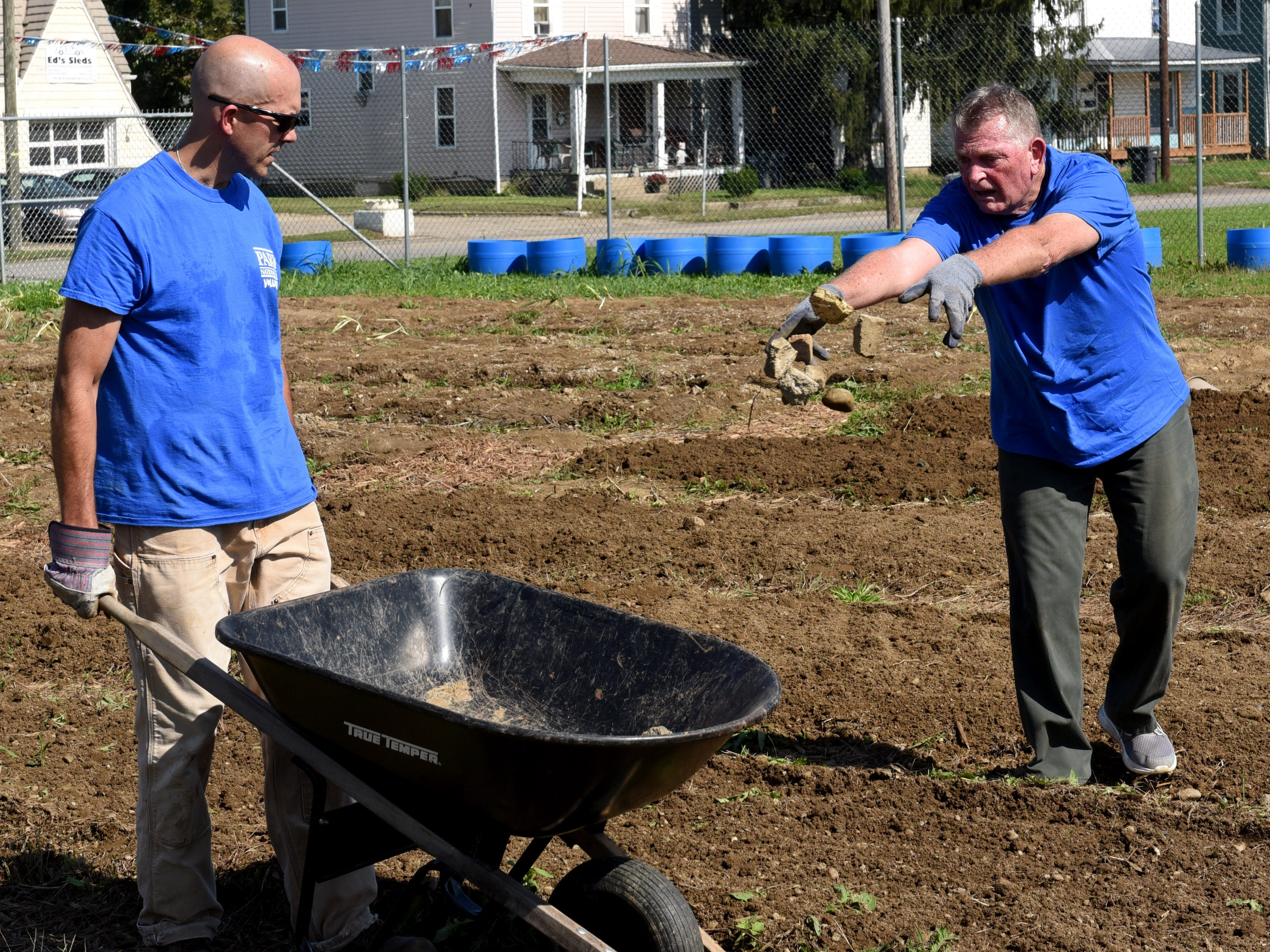 Park National Bank employee Phil West (right) tosses rocks in to a wheelbarrow held by PNB president David Trautman at the Together We Grow Garden on East Main Street in Newark. Bank employees volunteered at the garden to prepare it for winter as part of the company's PNB Cares initiative on Monday, Oct. 8, 2018. Employees worked on over 70 projects for organizations in Central Ohio communities. Local projects also included landscaping at the Weathervane Playhouse, organizing books for the Licking County Library, and painting for the Licking County Coalition for Housing.
