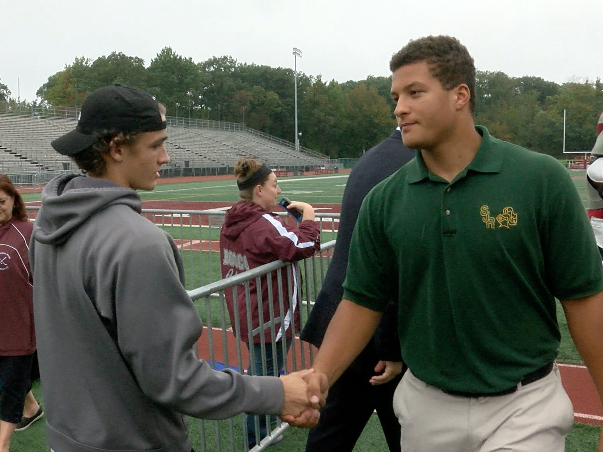 St. Joe's defensive lineman Howard Cross (right) shakes hands with Don Bosco wide receiver Christian Dremel during a break in the Red Zone Road Show shot at Don Bosco Prep Monday October 8, 2018.