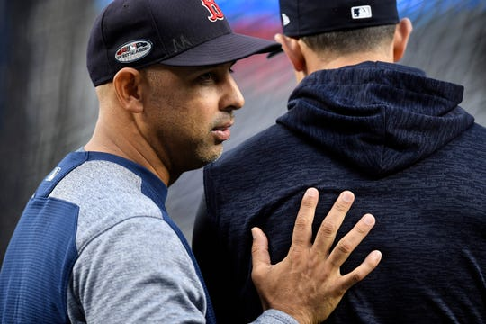 Red Sox manager Alex Cora, left, talks with Yankees manager Aaron Boone during batting practice before Game 3 of the American League Division Series on Monday, Oct. 8, 2018, in New York.