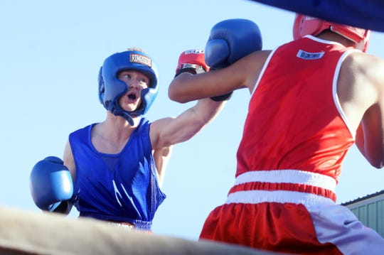 Superior Boxing Club fighter Ezekiel Sanoval, left, delivers a jab during his bout during Saturday's Fairground Throw-Down amateur boxing event at the Southwestern New Mexico State Fair.