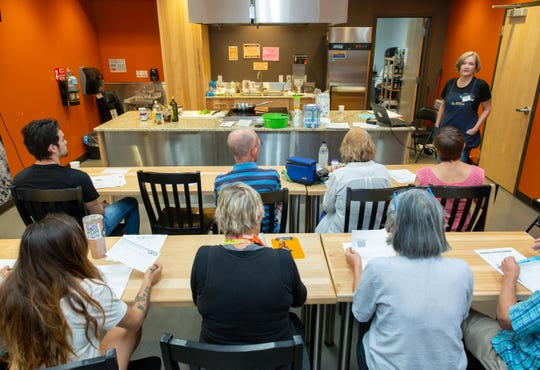 Attendees at a cooking class at Natural Grocers in Las Cruces listen to instruction from Marianne McLaughlin, who will help lead the classes about meal planning for children with autism.