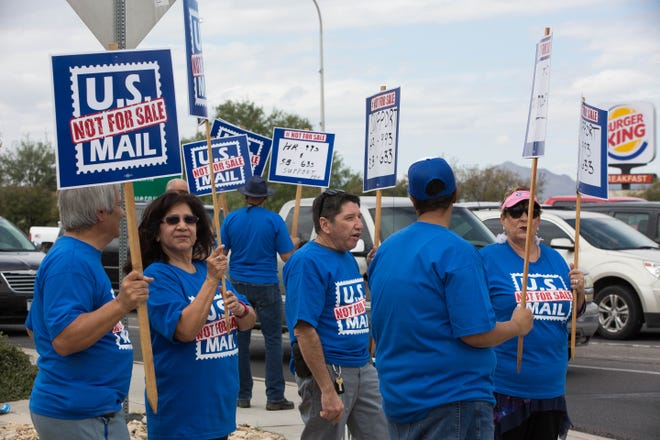 Members of the American Postal Workers Union Local 402 protest the privatization of the USPS on Monday Oct. 8, 2018, at the corner of Lohman Avenue and Telshor Boulevard.