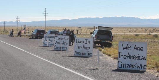 Demonstrators with the Tularosa Basin Downwinders set up signs outside of the White Sands Missile Range, where they advocate for financial compensation for those affected by the Trinity Test.