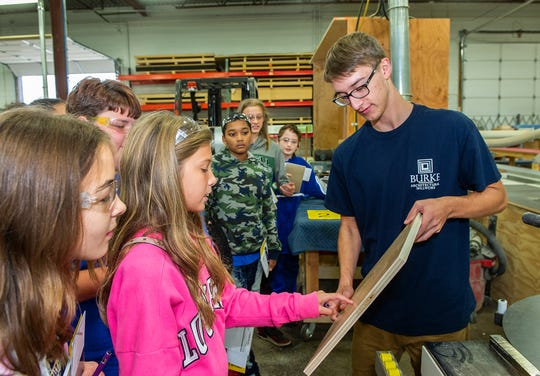 Weston Peterson from Burke Architectural Millwork shows students from Clarenceville Middle School wood grain patterns in a work-in-progress.