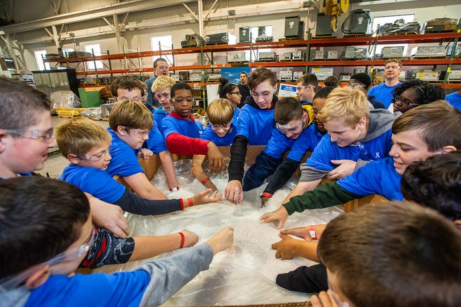 Students from Livonia's Emerson Middle School experience the texture of plastic pellets used in a plastic injection molder at Linear AMS in Livonia.