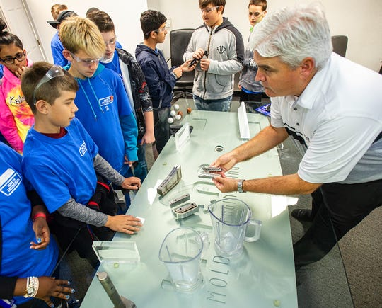 Linear AMS' Business Development Manager Brian Garvey shows injection molded parts to students from Emerson Middle School.