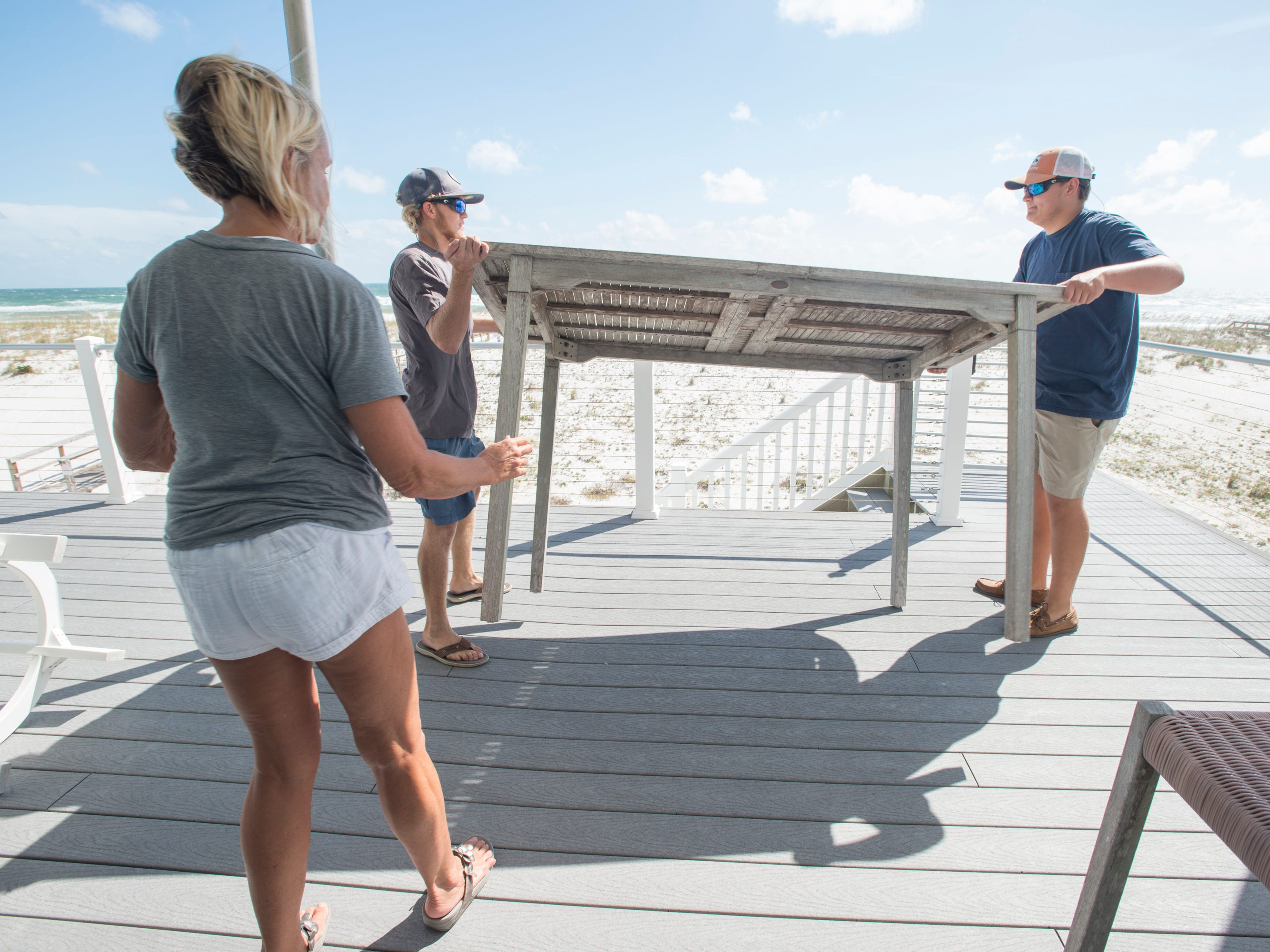 Homeowner Sharla Gorder supervises Jake Moore, right, and Mason O'Daniel as they remove patio furniture from her beachside house as Huricane Michael approaches the Florida panhandle on Monday, October 8, 2018.