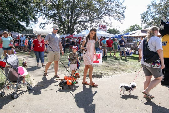 Owners walk their costumed pets in the pet parade during the last day of the 29th annual Jay Peanut Festival on the Gabbart Farm in October 2018.