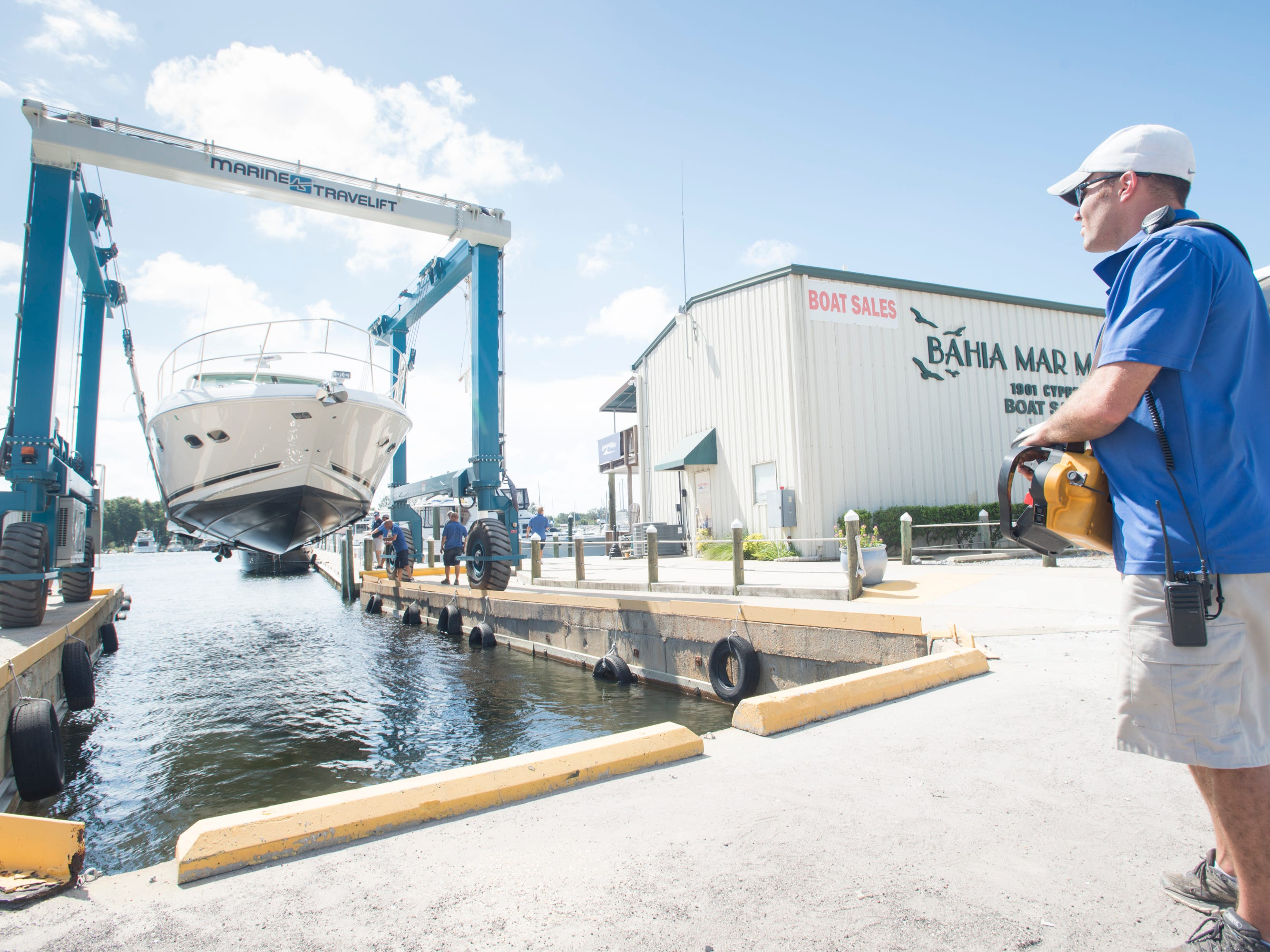Travel lift operator Greg SChiller, right, and fellow MarineMax Pensacola at Bahia Mar workers remove a boat from the water as Huricane Michael approaches the Florida panhandle on Monday, October 8, 2018.