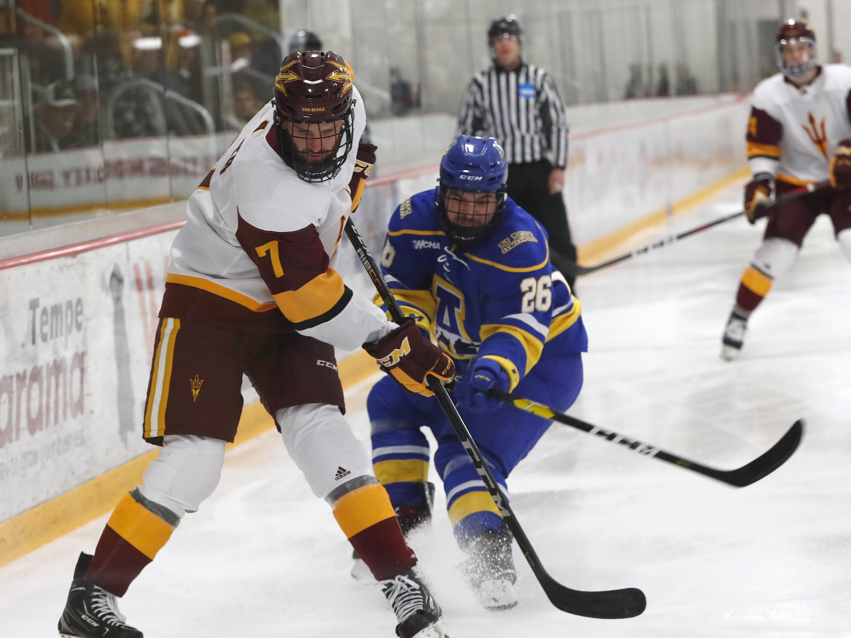 ASU's Johnny Walker (7) passes the puck against Alaska's Tyler Cline (26) at Oceanside Ice Arena in Tempe, Ariz. on October 7, 2018.