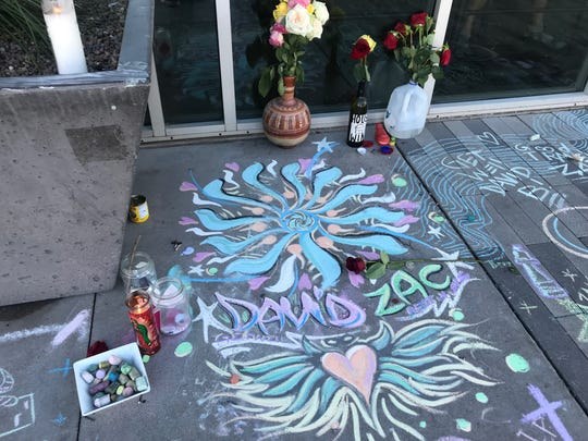 Candles, flowers and messages left in front of Jobot's Coffee and Diner for two employees who were fatally shot Friday.