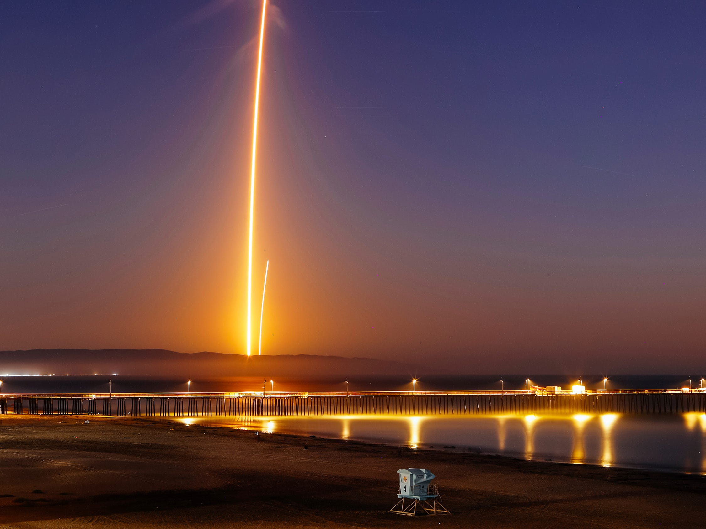 Two streaks in this long exposure photo show a SpaceX Falcon 9 rocket lifting off  from Vandenberg Air Force Base, as seen from Pismo Beach, Calif., on Sunday, Oct. 7, 2018, and then its first stage returning (right) to Earth at a nearby landing pad.