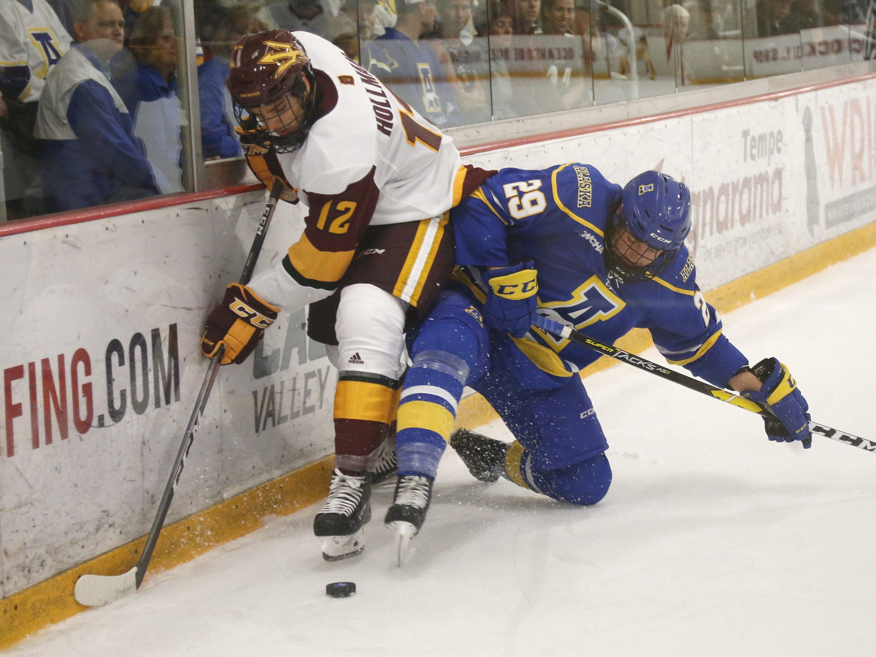 ASU's Dylan Hollman (12) tries to win a puck against Alaska's Chris Jandric (29) at Oceanside Ice Arena in Tempe, Ariz. on October 7, 2018.
