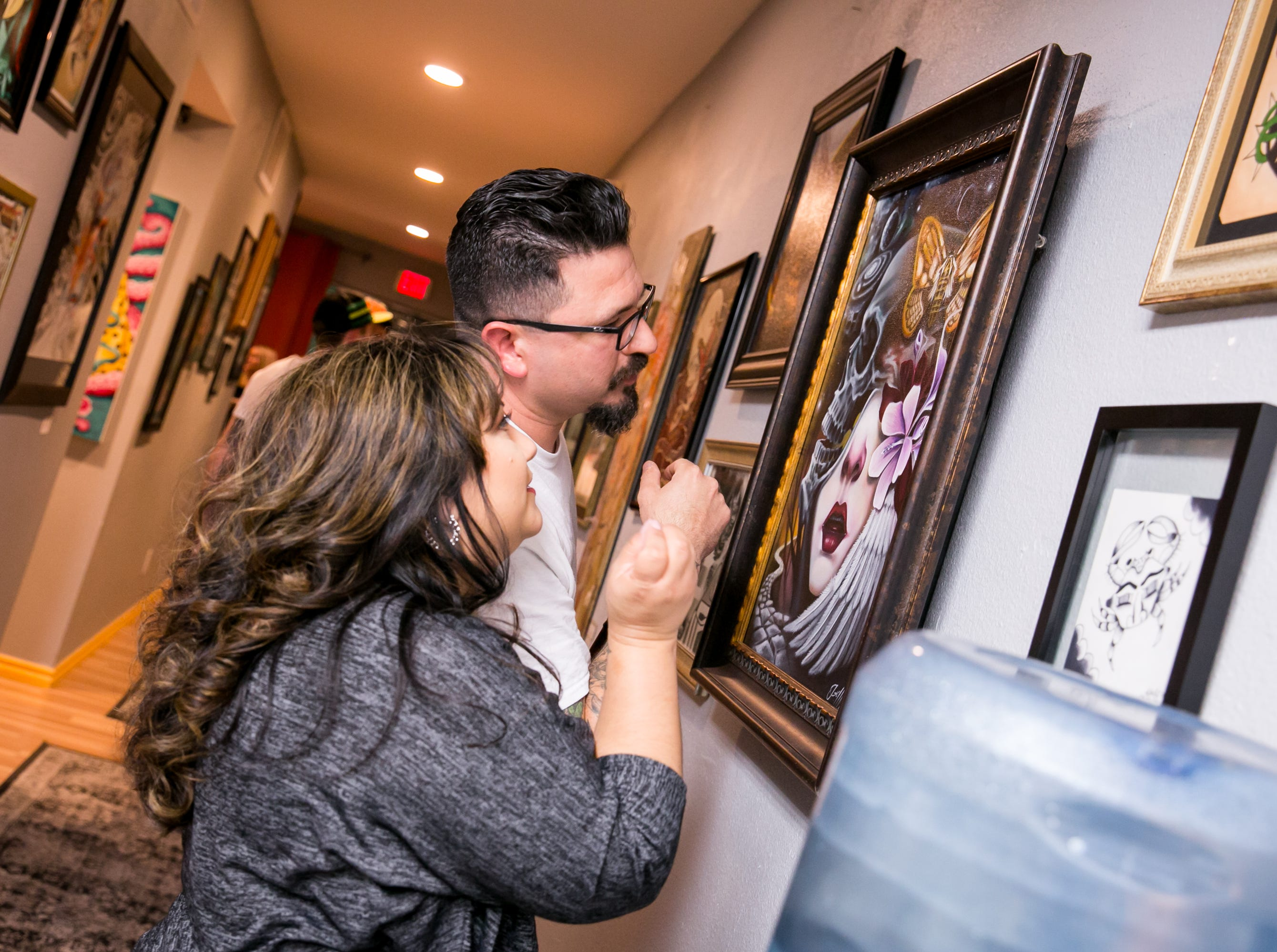 Attendees scope out the art during The Heart of Town tattoo art show at Lighten Up Laser during First Friday on October 5, 2018.