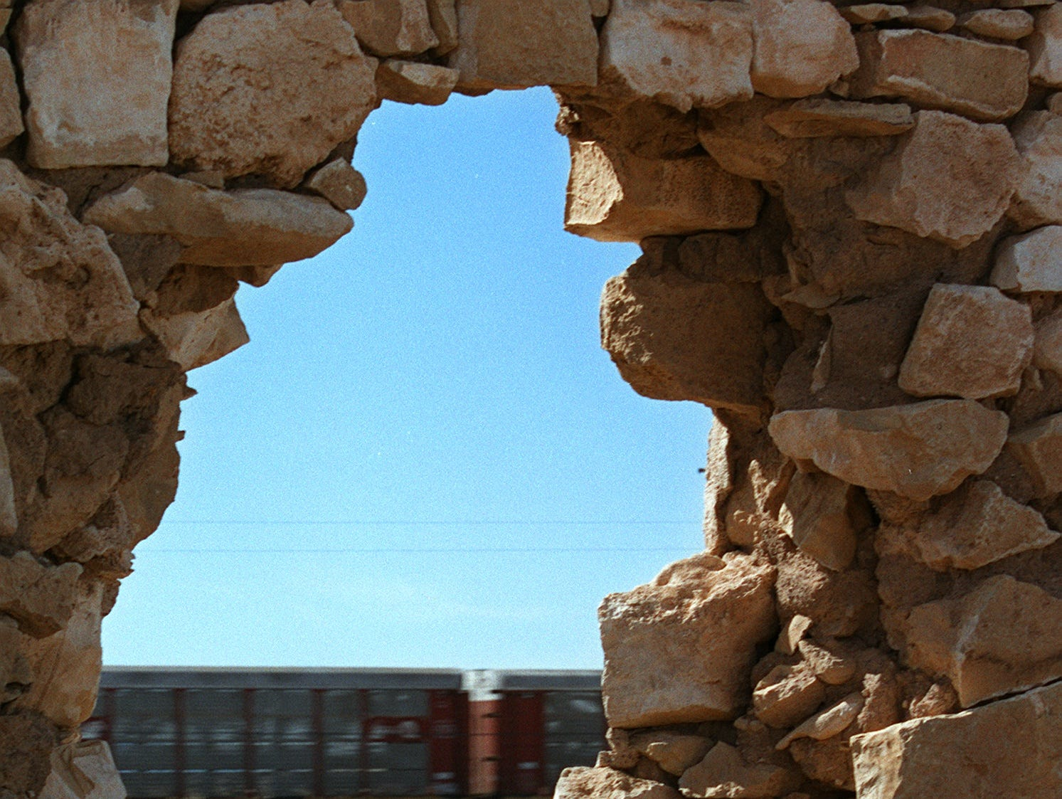 A freight train passes by the ruins of the trading post built on the site of the ghost town of Canyon Diablo.  The trading post was destroyed by a fire during the 1930s.