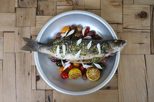Whole branzino gets flavor from Bar Pesce's wood fired grill.