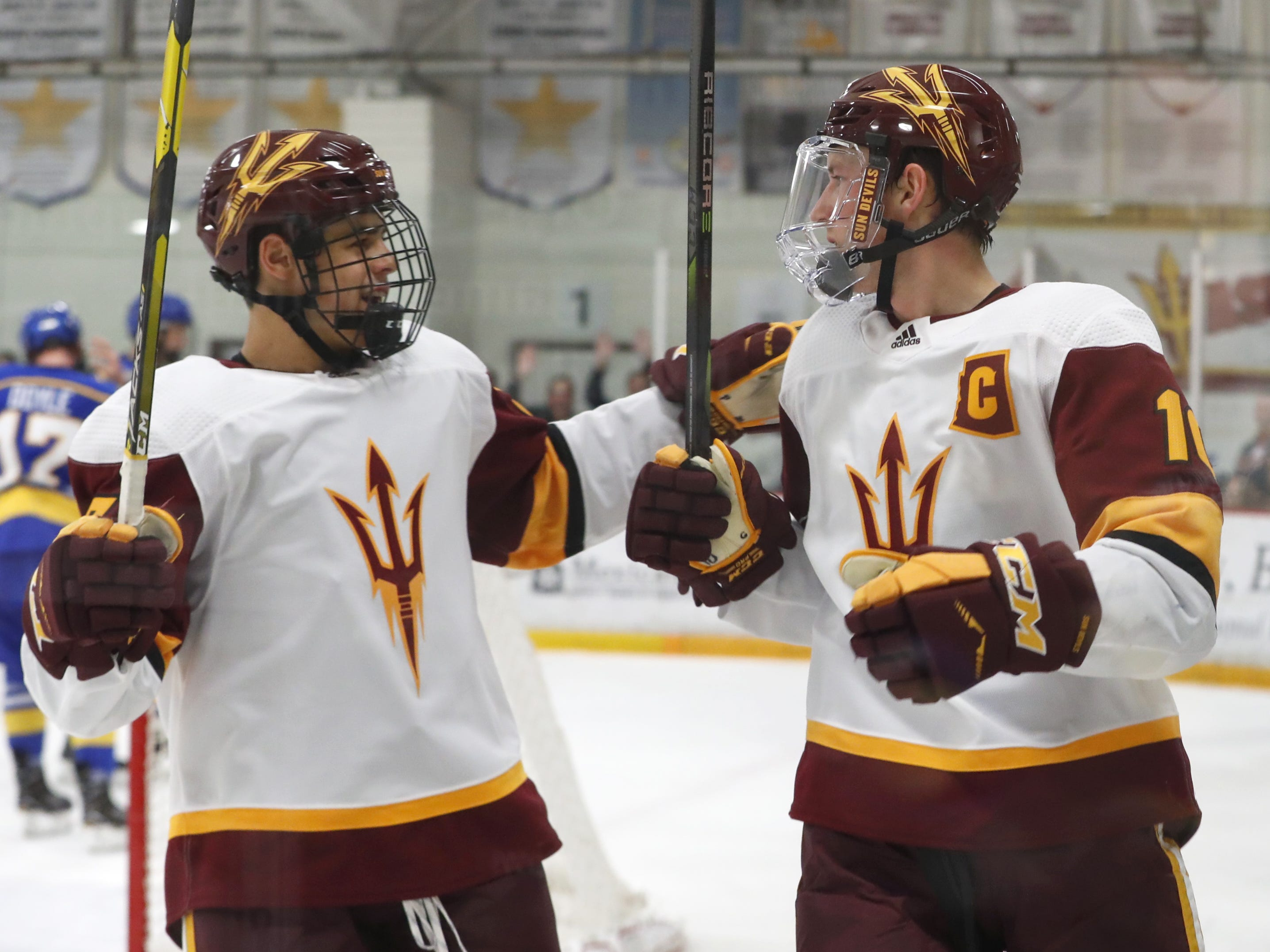 Alaska's Demetrios Koumontzis (23) celebrates with teammate Tyler Busch (10) after Busch scored against Alaska at Oceanside Ice Arena in Tempe, Ariz. on October 7, 2018.